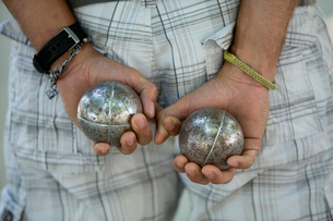 A boules player with one metal ball in each hand, held behind his back.の写真素材 [FYI02249840]