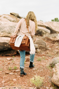 Woman walking past rocks in a desert, carrying a leather bag.の写真素材 [FYI02249842]