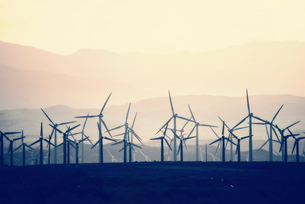 Wind power turbines in the landscape. A large number of turbine powers on a plain against a mountainの写真素材 [FYI02249845]