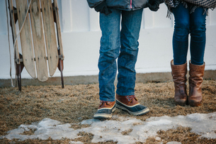 Two young people, a boy and girl standing in a yard in winter.の写真素材 [FYI02249847]
