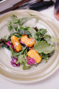 A plate of fresh salad leaves and slices of fresh peach fruit.の写真素材 [FYI02249855]
