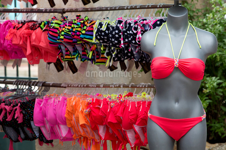 A clothes stall in the market, and a rack of women's swimwear. A pink bikini on a mannequin.の写真素材 [FYI02249858]