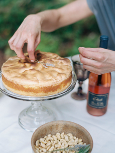 A woman decorating a cake on a glass stand. A dish of nuts and a bottle of rose wine.の写真素材 [FYI02249873]
