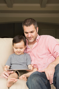 Smiling man sitting on a sofa with his young son, looking at a digital tablet.の写真素材 [FYI02249882]