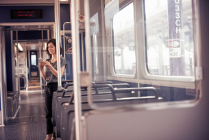 A woman standing alone on a bus checking her cell phoneの写真素材 [FYI02249889]