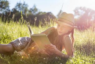 A young girl in a straw hat lying on the grass reading a book.の写真素材 [FYI02249896]