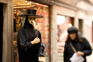 A person in a bird mask, a traditional carnival costume, with a long bird beak. A woman walking by.の写真素材 [FYI02249902]