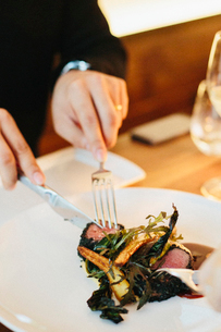A man seated using a knife and fork eating meat and roasted vegetables.の写真素材 [FYI02249920]