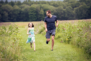 A man and a young child running through a wildflower meadow.の写真素材 [FYI02249937]