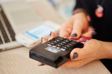 A woman's hands holding a credit card reader, 有ocessing payment or paying for goods.の写真素材 [FYI02249940]