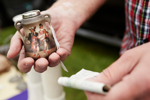 Close up of a man holding a vintage pot and British currency, cash, at a flea market.の写真素材 [FYI02249965]