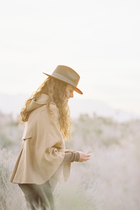 A woman in a warm coat and a hat picking wild flowers.の写真素材 [FYI02249987]