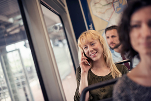 A blond woman on a city bus, talking on her smart phoneの写真素材 [FYI02250006]