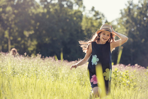 A child, a young girl in straw hat in a meadow of wild flowers in summer.の写真素材 [FYI02250007]
