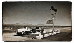A truck towing a trailer parked at a roadside stop on a desert highway.の写真素材 [FYI02250035]