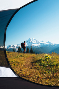 View from inside a camping tent of a man hiking across national forest land with Mount Baker in theの写真素材 [FYI02250041]