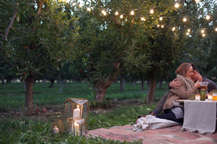 An apple orchard in Utah. Couple sitting on the ground, embracing, food and drink on a table.の写真素材 [FYI02250043]