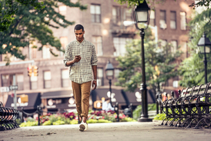 A man walking through a town square looking at his smart phoneの写真素材 [FYI02250049]