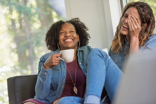 Two women seated on a sofa, laughing together, one holding a large coffee cup.の写真素材 [FYI02250090]