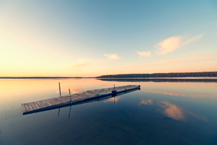 A wooden dock floating on flat calm waters of a lake at sunset.の写真素材 [FYI02250105]