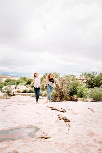 Two women running barefoot across the sand in a desert landscapeの写真素材 [FYI02250148]
