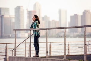 A woman standing on the waterfront, view to the city over the water in New York City.の写真素材 [FYI02250152]