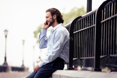 A man seated on a step on the street, making a call.の写真素材 [FYI02250153]