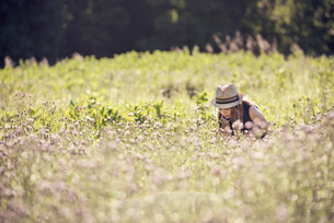 A child, a young girl in straw hat in a meadow of wild flowers in summer.の写真素材 [FYI02250165]