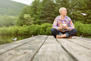 A woman sitting outdoors on a dock with a cup of coffeeの写真素材 [FYI02250169]