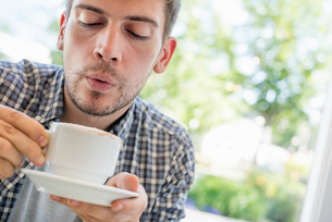 A man blowing on the surface of his hot coffee.の写真素材 [FYI02250188]