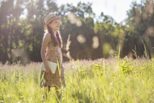 A child in a straw hat walking through long grass carrying a book.の写真素材 [FYI02250193]