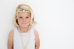 Young girl wearing a tiara and a pearl necklace, posing for a picture in a photographers studio.の写真素材 [FYI02250196]