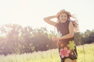A child, a young girl in straw hat in a meadow of wild flowers in summer.の写真素材 [FYI02250210]