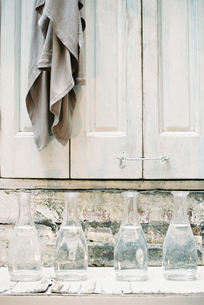 A cloth hanging from a peg on a  cupboard door, above a shelf of glass carafes.の写真素材 [FYI02250211]