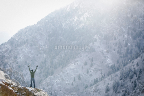 A man greeting the sun, with his arms raised on a rock outcrop in the mountains.の写真素材 [FYI02250218]