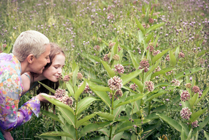 A mature woman and a young girl in a wildflower meadow looking closely at the flowers.の写真素材 [FYI02250224]