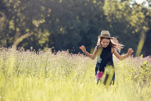 A child, a young girl in straw hat in a meadow of wild flowers in summer.の写真素材 [FYI02250242]