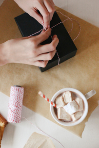 A person wrapping a parcel and a jar of homemade marshmallows.の写真素材 [FYI02250246]