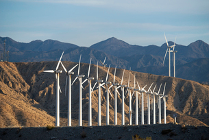 Wind power turbines in the landscape. A large number of turbine powers on a plain against a mountainの写真素材 [FYI02250249]