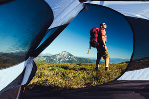 View from inside a camping tent of man hiking across national forest land with Mount Baker in the diの写真素材 [FYI02250272]