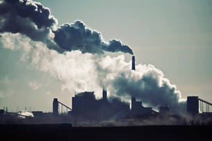 Heat, steam and smoke rising from the chimneys of a power plant against the sky.の写真素材 [FYI02250274]
