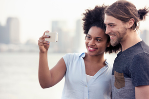 A couple, man and woman taking a selfie by the waterfront in a cityの写真素材 [FYI02250277]