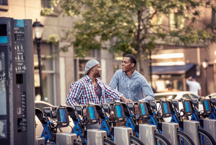 Two men by a rack of bicycles for hire in a city parkの写真素材 [FYI02250287]