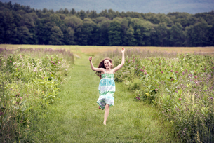 A girl running through a meadow with her arms above her head.の写真素材 [FYI02250292]