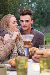An apple orchard in Utah. A couple embracing, food and drink on a table.の写真素材 [FYI02250301]