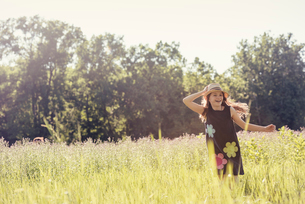 A child, a young girl in straw hat in a meadow of wild flowers in summer.の写真素材 [FYI02250302]