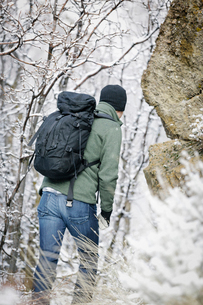 A man wearing a fleece jacket and hat, carrying a rucksack, climbing up a rocky slope.の写真素材 [FYI02250305]