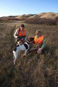 Two men, bird hunters, with shotguns, carrying the day's bag of dead birds, and a spaniel dog.の写真素材 [FYI02250314]