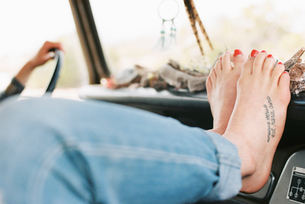 Barefoot woman resting her feet on the dashboard of a 4x4, a tattoo on her right foot.の写真素材 [FYI02250323]