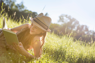 A young girl in a straw hat lying on the grass reading a book.の写真素材 [FYI02250368]